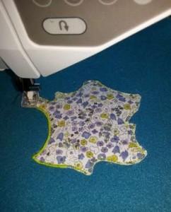 Appliqué en tissu liberty bleu et vert anis, en forme de carte de France, en train de se réaliser, sur tissu polaire bleu électrique