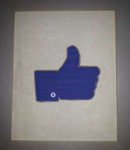 Appliqué bleu en forme de like Facebook, apposé sur toile de lin couleur naturelle.