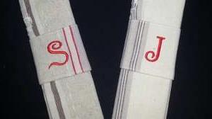 Lettres brodées en rouge sur ronds de serviettes en tissu.