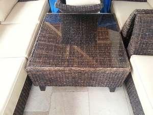 Table de salon de terrasse 90*90, en rotin et verre, à protéger pour l'hiver.