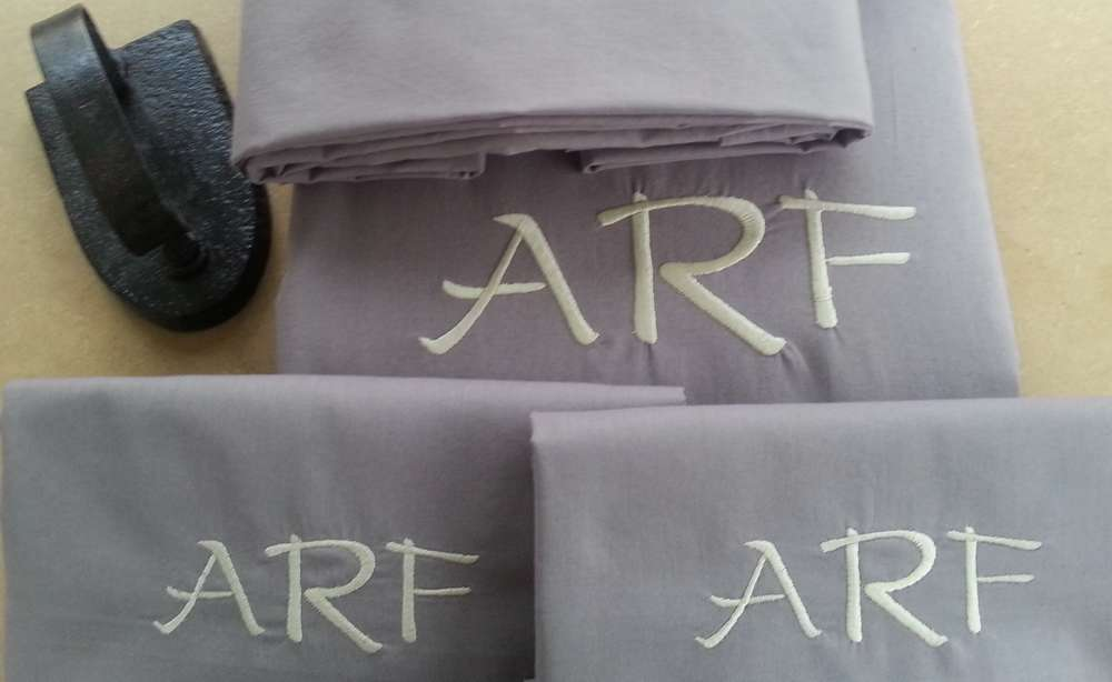 Draps taupes brodés aux initiales ARF