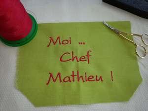 """Inscription brodée en rouge """"Moi Chef Mathieu !"""" sur poche vert anis du tablier de cuisine."""