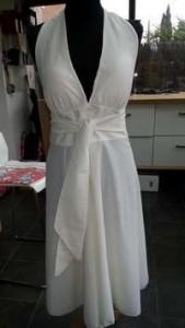 Robe blanche façon Marylin, grand décoletté devant, nouée sur la nuque et dos nue, cintrée à la taille avec ceinture large, jupe enforme. Le tout dans un tissu fluide et léger.