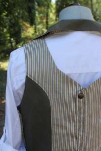 Gilet pour femme, avec empiècement tissu rayures au dos, et ouverture en haut du dos. Pince et pression au milieu dos.