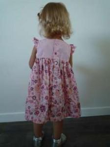 Robe d'été fillette, à manches avec volants, empiècement du haut en coton doublé rose tendre uni et bas de la robe froncé en coton imprimé rose façon japonisant. Robe vue de dos et boutonnée de bas en haut.