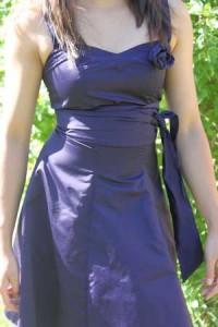 Robe en taffetas bleu nuit, bustier et avec bretelles, cintrée à la taille, agrémentée d'une ceinture assortie. Courte, jupe enforme, décoration par fleur en tissu assorti sur bustier.